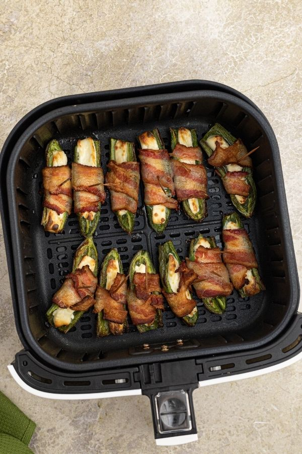 Cooked Jalapeños wrapped in bacon in the air fryer basket.
