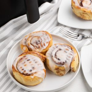 Pillsbury Cinnamon Rolls made in the air fryer ond served on a white plate.