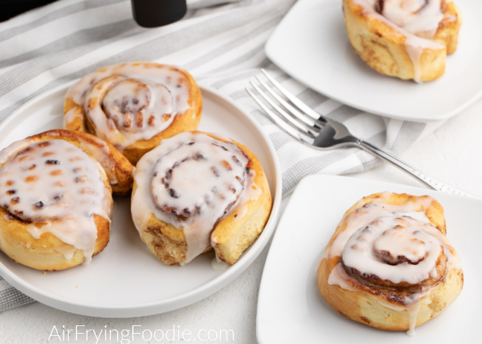 Cinnamon rolls covered in glaze on white plates made in the Air Fryer.