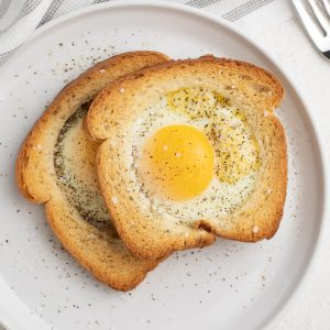 Eggs in a basket made in the Air Fryer and served on a white plate, sprinkled with salt and pepper.