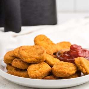 Air Fryer Frozen Chicken Nuggets on a white plate with ketchup dipping sauce.