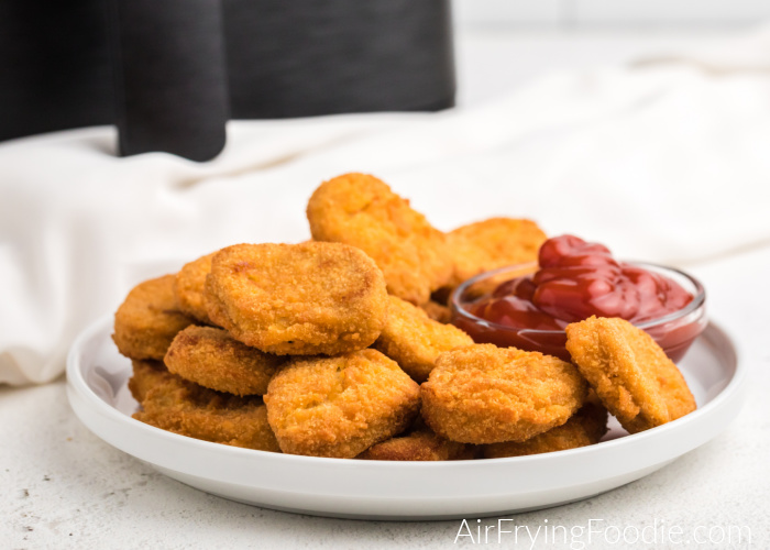 Air Fryer in the background and chicken nuggets on a white plate with a small bowl of ketchup.
