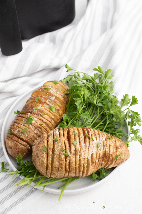 Hasselback Potatoes made in the Air Fryer and covered with parmesan cheese and fresh parsley on a white plate.