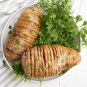 Close up sliced potatoes on a white plate with parsley garnish