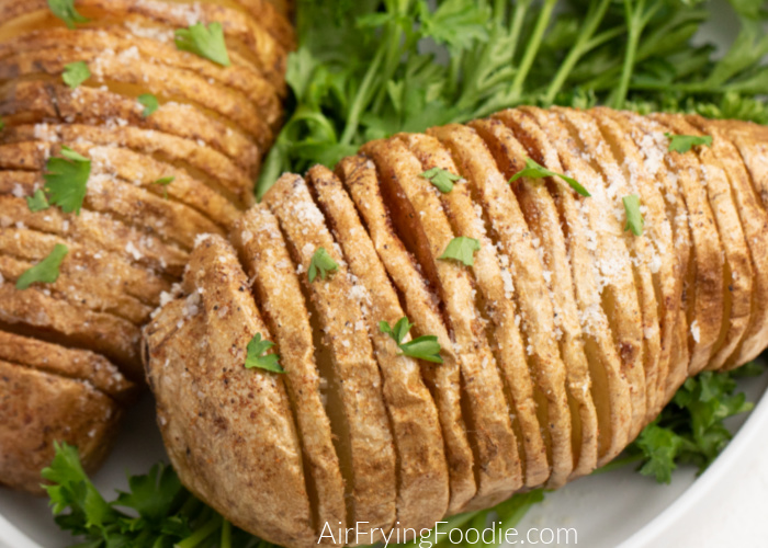Air Fryer Hasselback Potatoes on a white plate covered in fresh parmesan cheese and parsley.