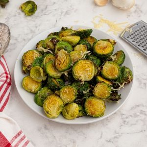 Cooked parmesan brussel sprouts, served on a white plate.