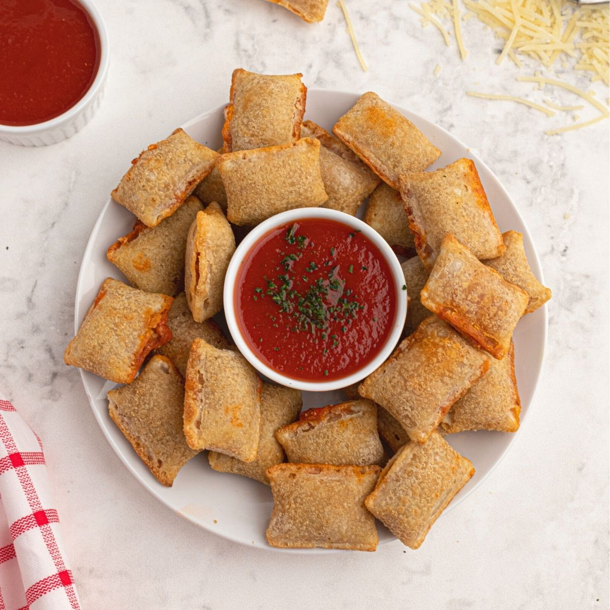 Cooked pizza rolls cooked and served on a white plate with shredded parmesan cheese and red dipping sauce.