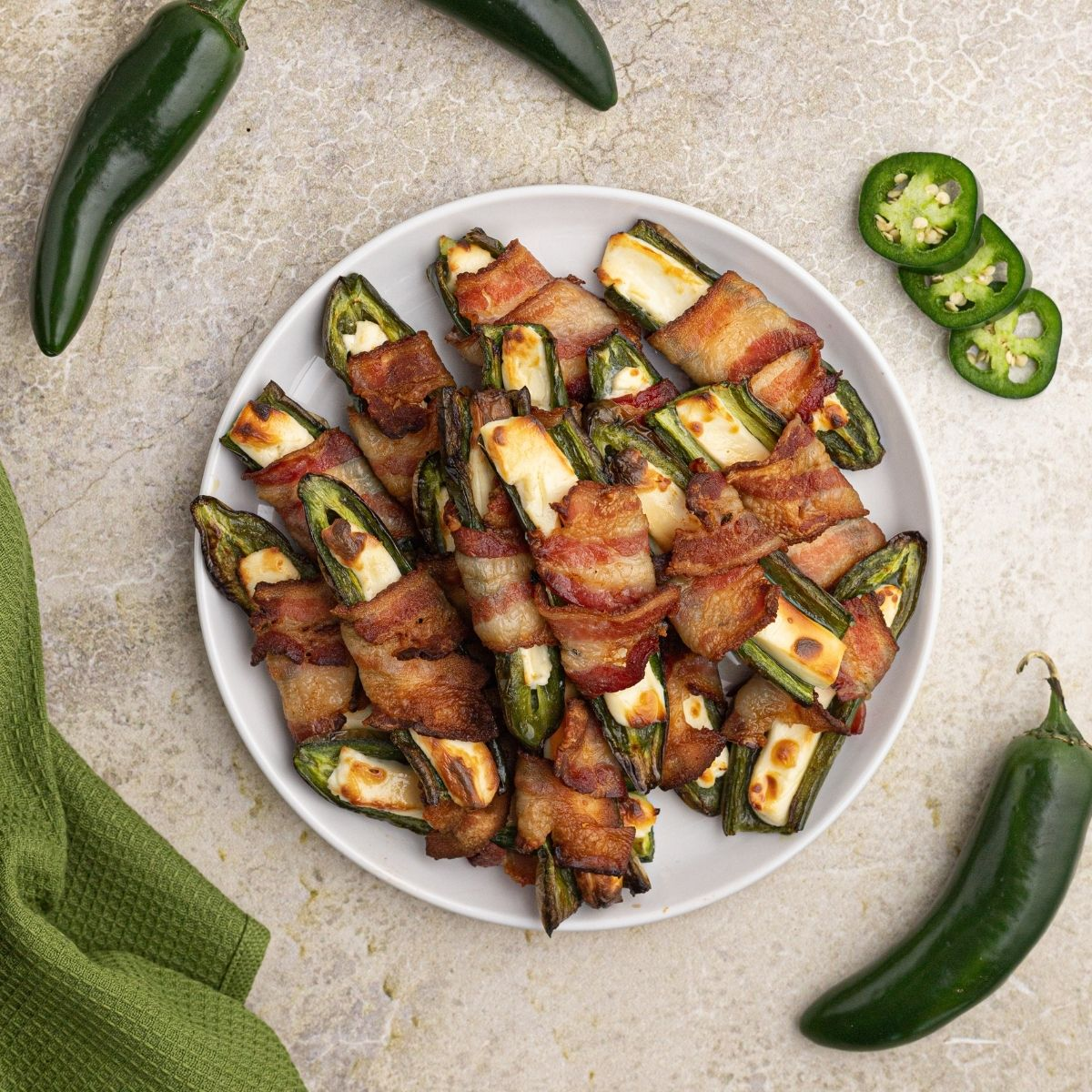 Air Fryer Jalepeno Poppers stuffed with cream cheese and wrapped in bacon, serve on a white plate