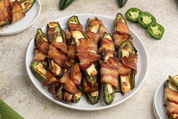 Air Fryer Jalepeno Poppers wrapped in cooked bacon strips on white plates