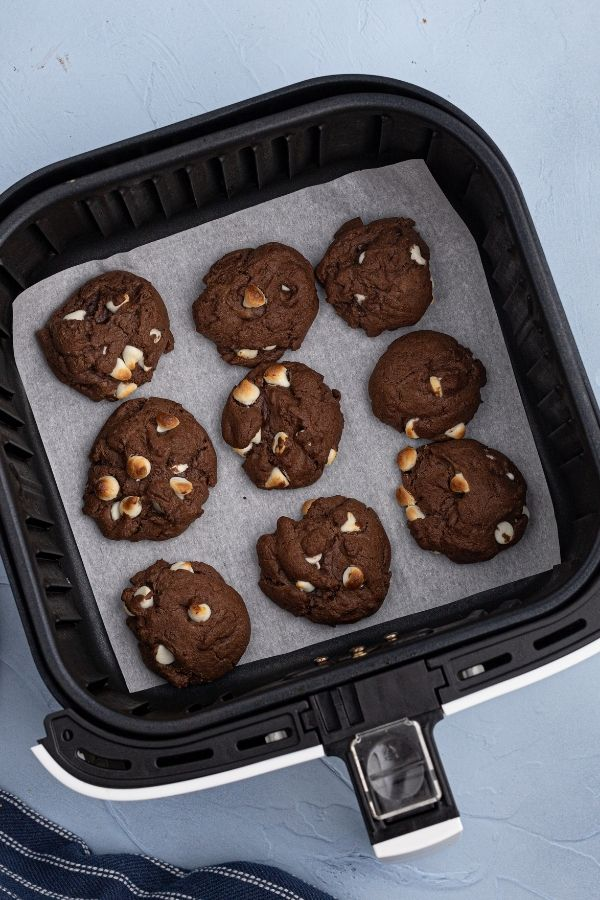Cookies after they have finished cooking, on parchment paper in the air fryer basket