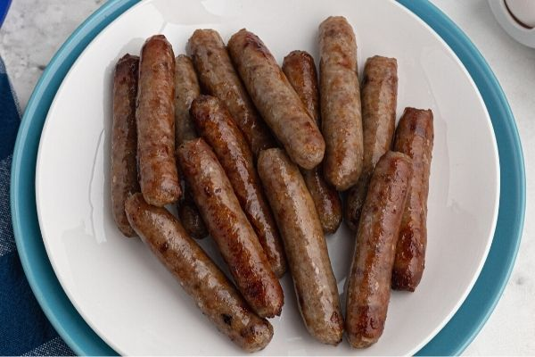 Cooked juicy sausage links, served on a white plate.