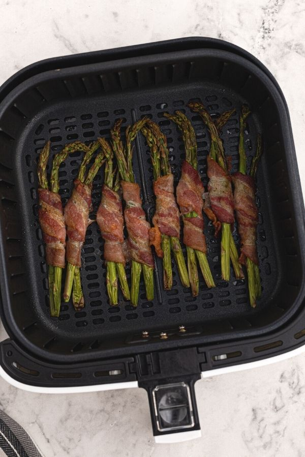 Cooked bacon wrapped around asparagus in the air fryer basket