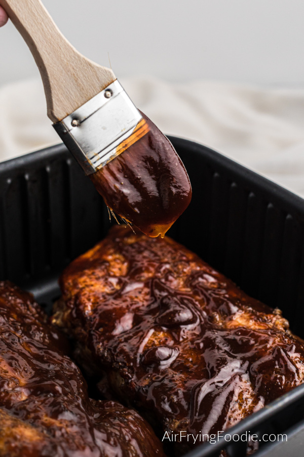 Air Fryer Ribs being slathered with BBQ sauce before serving.