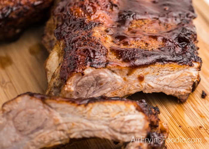 BBQ Ribs made in the Air Fryer and covered in BBQ sauce on a chopping block.