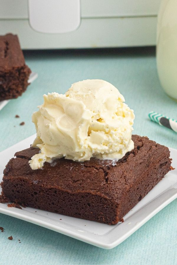 Air Fryer Brownie, sliced and served on a white plate with vanilla ice cream on top.