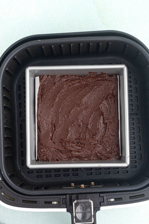 Uncooked brownie in a pan, inside the air fryer basket.