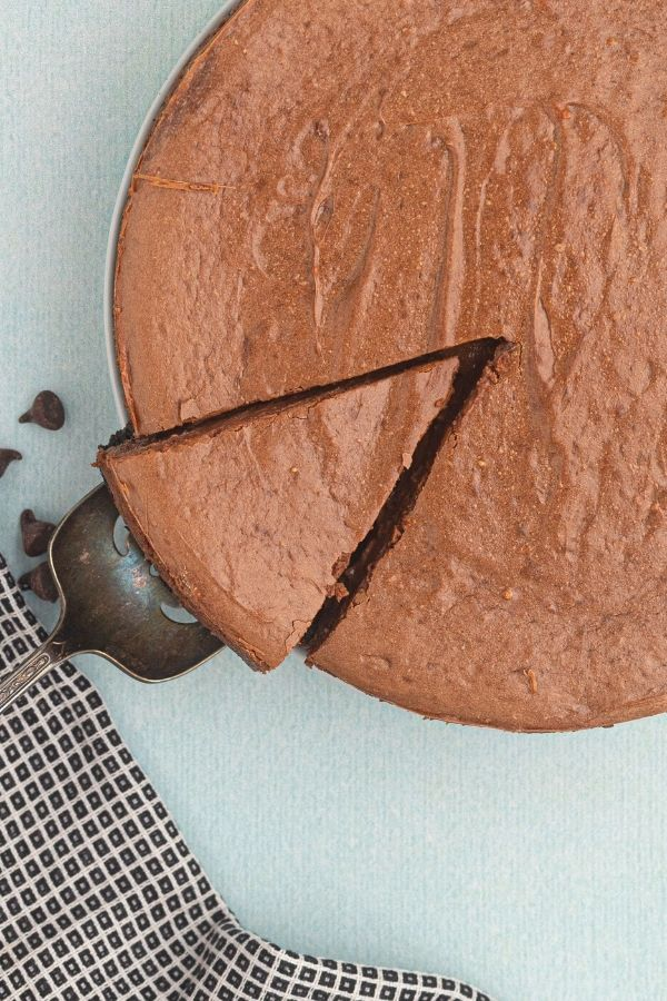 Air Fryer chocolate cheesecake with a slice cut, being lifted on a spatula.