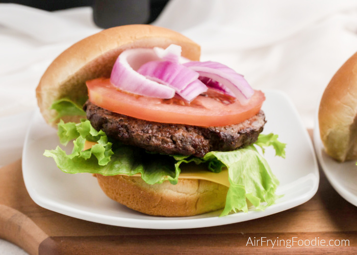 Air Fried hamburger on a bun with lettuce and tomato and onion.