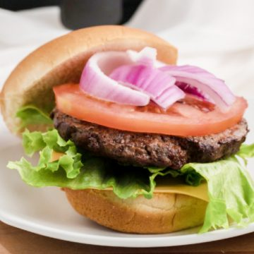 Air Fried hamburger pattie on a bed of lettuce with cheese, tomato, and onion.