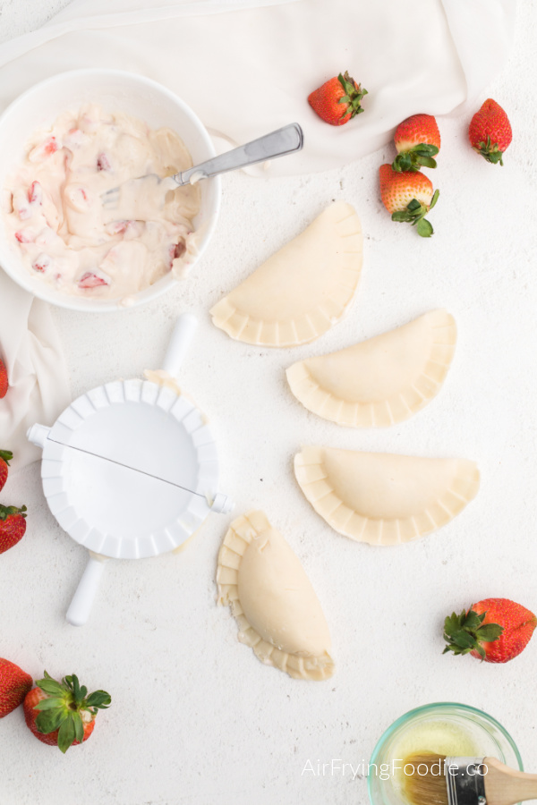 Steps to make strawberry cream cheese hang pies before placing them into the Air Fryer.