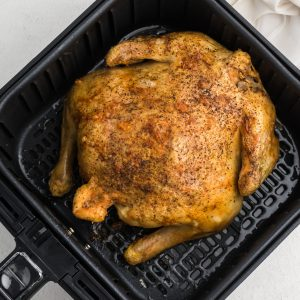 Fully cooked whole chicken in Air Fryer basket.