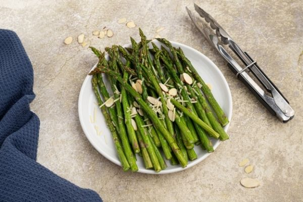 Cooked, green asparagus, served on a white plate. Crispy asparagus with almond slivers and shredded parmesan.