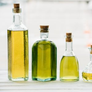 Different oils in bottles on a counter top.