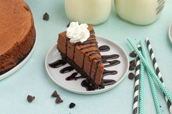 Slice of chocolate cheese cake on a white plate drizzled with chocolate and topped with whipped cream.