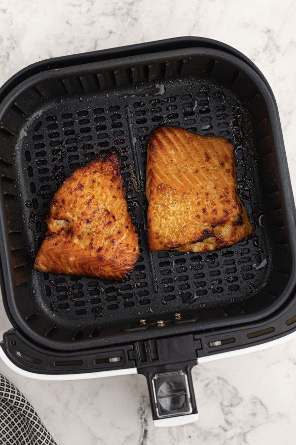 Cooked glazed honey mustard salmon, in the air fryer basket.