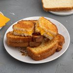 Cooked, golden crispy grilled cheese sandwich cut and served onto a white plate.