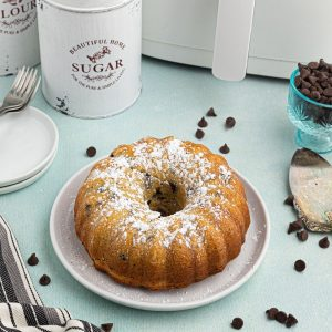 Round golden Bundt cake with chocolate chips scattered and in front of the air fryer.