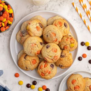 Baked sugar cookies scattered on a white plate, with Reece's Pieces candy scattered around the plate.