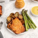 Cooked honey mustard glazed salmon served on a white plate with asparagus.