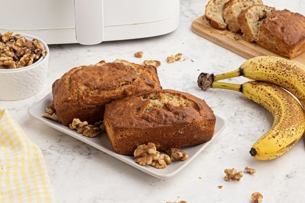 Two mini loaves of bread on a white square plate, with bananas and scattered walnuts.