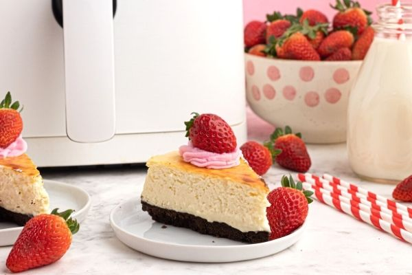 Cooked creamy cheesecake with a chocolate cookie crust, topped with strawberries.