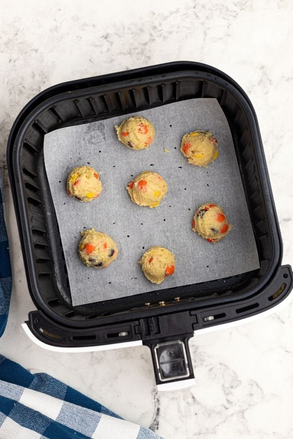 Uncooked sugar cookie dough in the air fryer basket.