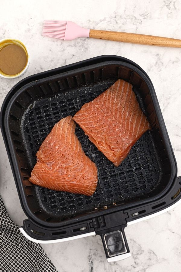 Un cooked salmon, seasoned, in the air fryer basket.