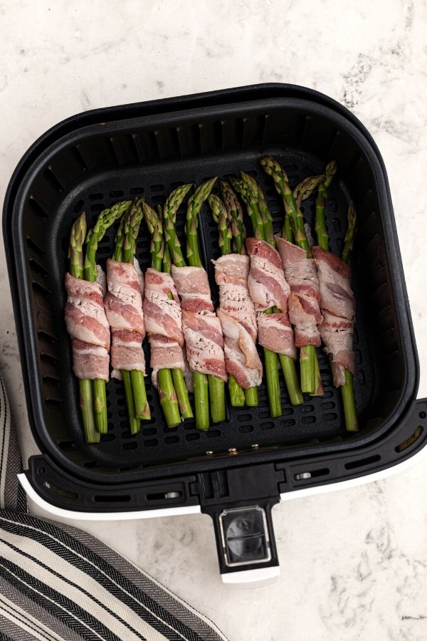 Uncooked bacon wrapped around asparagus in an air fryer basket.