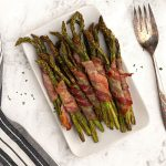 Crispy bacon wrapped asparagus served on a white plate