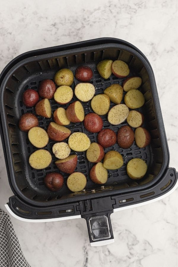 Uncooked cut and seasoned small potatoes, in an air fryer basket.