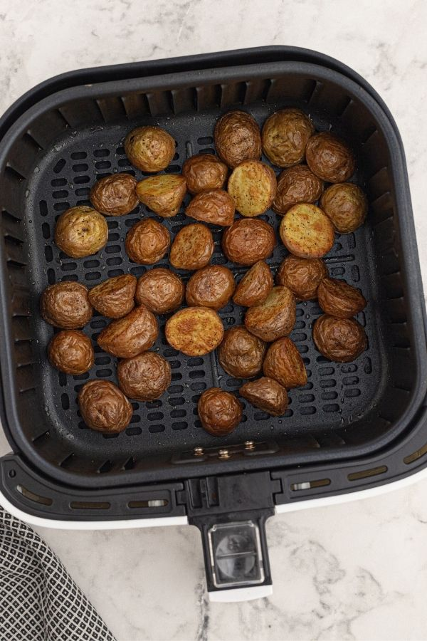 cooked small potatoes, cut into halves and seasoned in an air fryer basket.