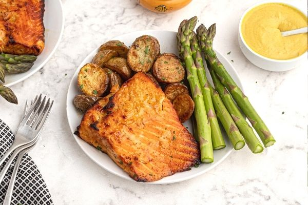 Crispy and golden salmon with a honey  mustard glaze, served on a white plate with asparagus and potatoes.