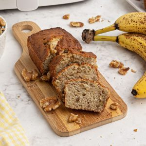 sliced loaf of banana nut bread in front of an air fryer next to bananas and scattered walnuts