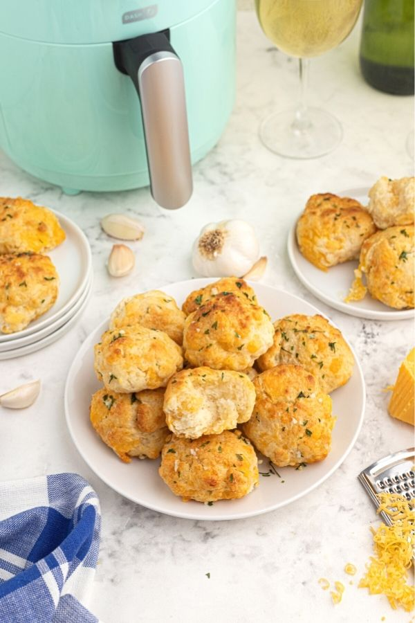 Golden cooked cheddar biscuits with parsley flakes on top, served on a white plate with shredded cheddar cheese and garlic cloves, scattered on the table. One biscuit is broken in half.