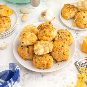 Golden cooked cheddar biscuits with parsley flakes on top, served on a white plate with shredded cheddar cheese and garlic cloves, scattered on the table.