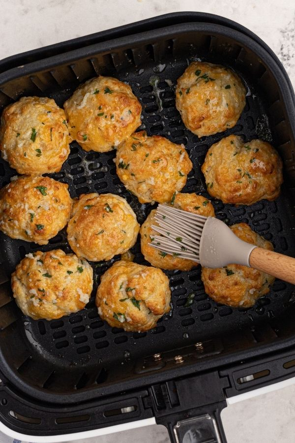Golden cheddar biscuits in the air fryer basket, being brushed with melted butter and garlic, topped with parsley flakes.
