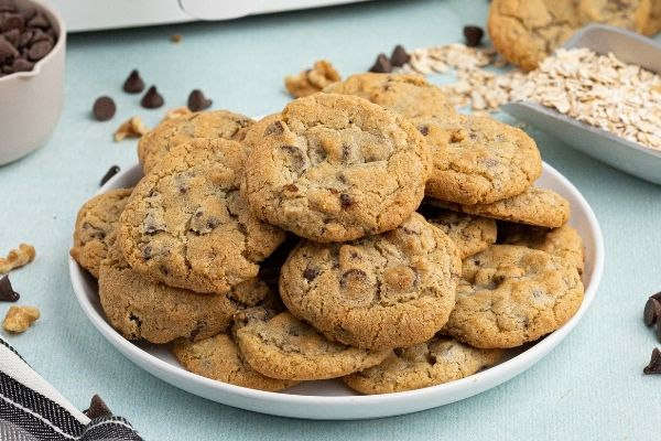 Golden chocolate chip cookies on a white plate with oats and chocolate chips scattered.