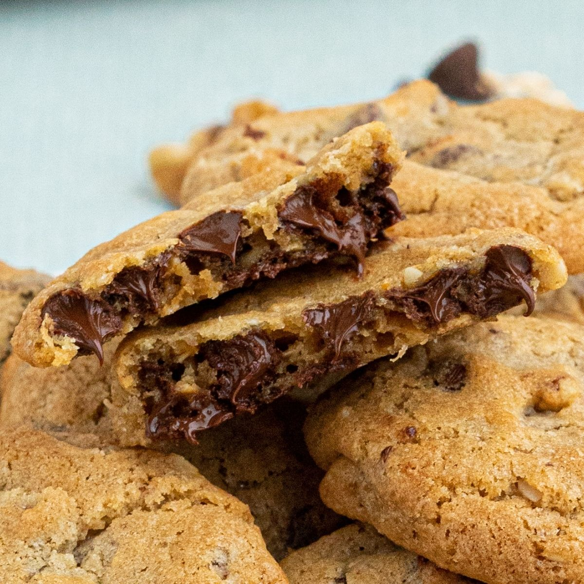 Close up photo of chocolate chip cookies with melting chocolate dripping out of cookie.