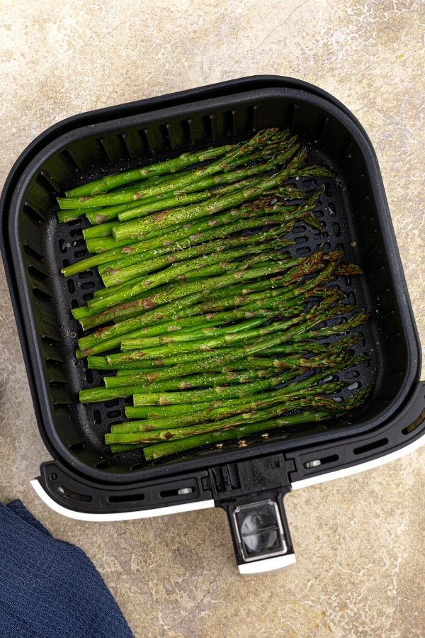 Cooked green asparagus, in the air fryer basket.