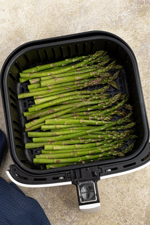 Uncooked green asparagus in the air fryer basket, seasoned with salt and pepper.